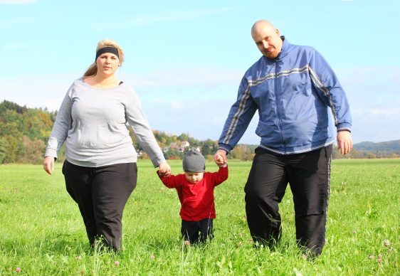 Overweight parents with her son walking together.